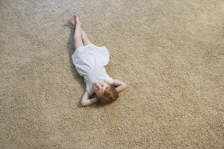 Girl Laying on Carpet Indoors