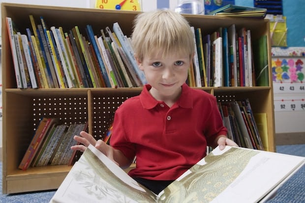 Child at Library Holding Book