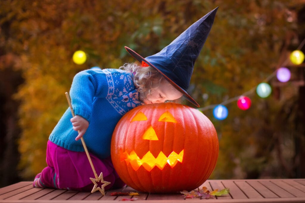 girl with witch hat and wand looking into jack o lantern pumpkin