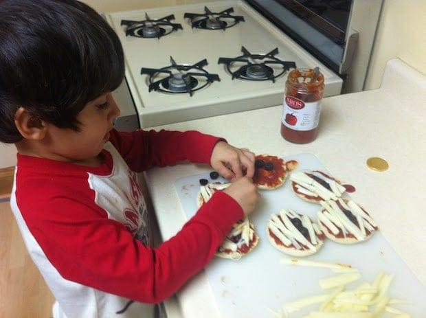 boy decorating mummy pizzas
