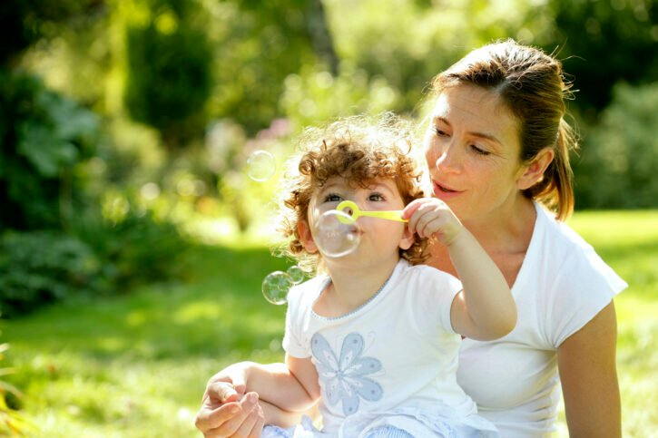 child blowing bubbles with mother