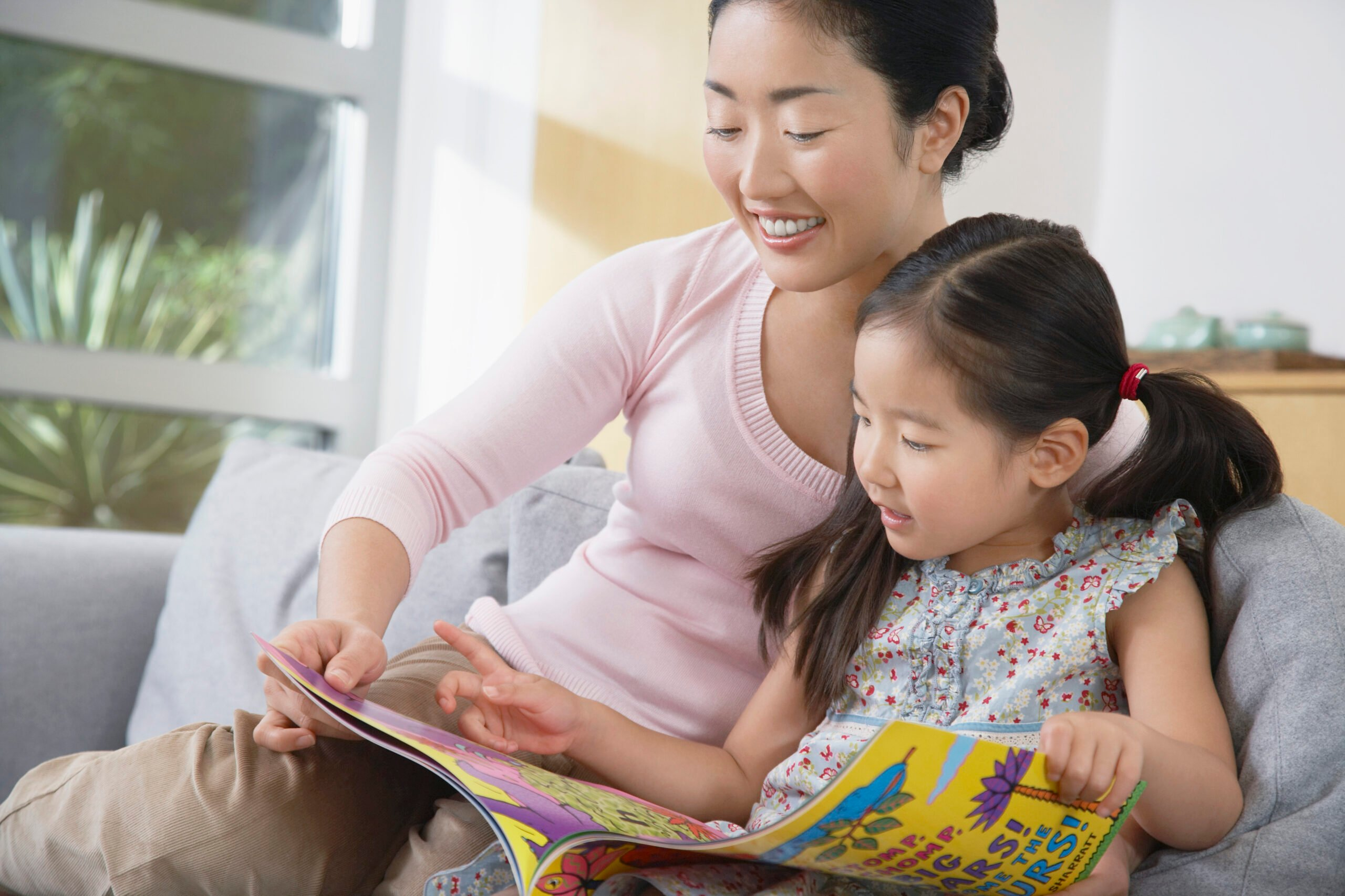 mother reading book with daughter
