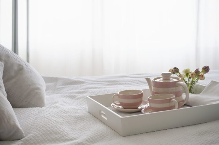 pink striped teaset in tray on bed