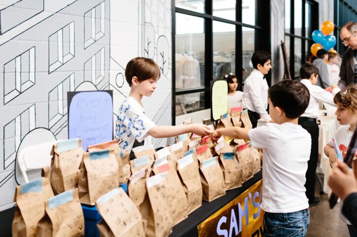 Boy behind table at Acton Children's Business Fair making sale in a brown paper bag to another boy