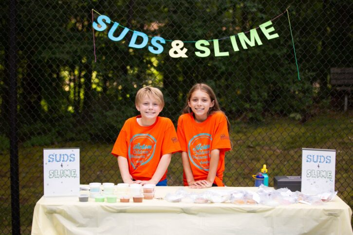 Boy and girl in orange shirts selling suds and slime at Acton Children's Business Fair